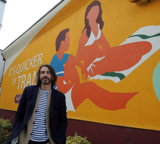 Image of Adrian Riley with a mural he created.